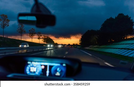 Passenger or driver point of view of driving a car along a highway at night with a colorful fiery orange sunset above the road and traffic ahead