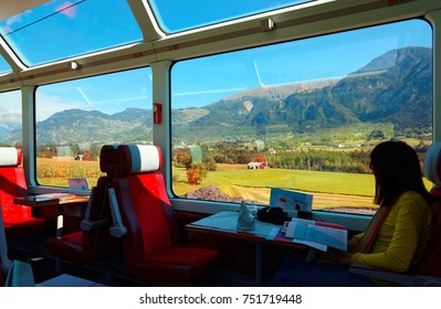 A passenger enjoying the idyllic scenery of Swiss countryside through the wide panoramic windows on the Glacier Express with sunlight cast thru the glass skylights on a sunny summer day in Switzerland