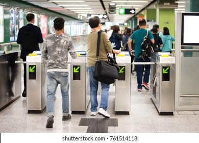 Passenger at entrance gate of subway.
