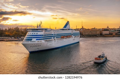 Passenger ferry and tugboat sail against Helsinki city in South Harbour at sunset, Finland