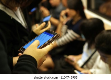 The passenger hand holding mobile phone devices inside MRT subway train, Smartphone usage lifestyle daily, Social technology telecommunication, Blurred screen