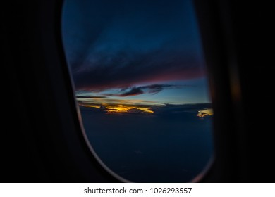 A passenger has a beautiful view of the setting sun from 30,000+ feet.