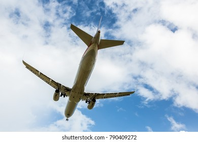 Passenger Jet Aircraft Flying Overhead against Cloudy Sky