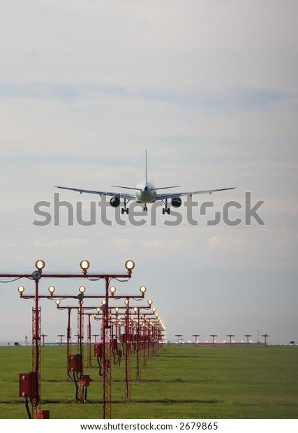 passenger jet over runway marker lights