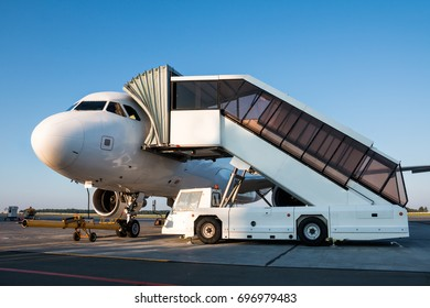 Passenger jet plane with boarding steps at the airport apron