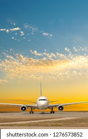Passenger jet plane on the runway in the airport front view on sunset