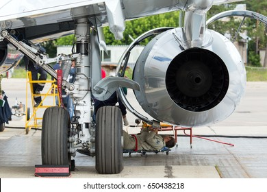 Passenger jet plane in service. Airplane maintenance. Engineer and technician repair aircraft engine.