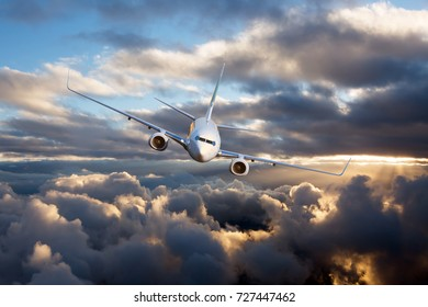Passenger jet plane in the sky. Airplane flies high above the storm clouds.
