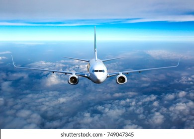Passenger jet plane in the sky. Airplane flies high through the clouds. Aircraft front view.