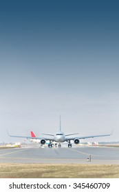 Passenger jet planes are taxiing to the runway for a takeoff
