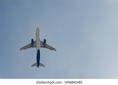 A passenger jet taking off and silhouetted against the blue sky. The plane is flying with passengers on a journey.
