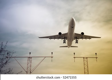 passenger jet taking-off or landing through color gradient clouds