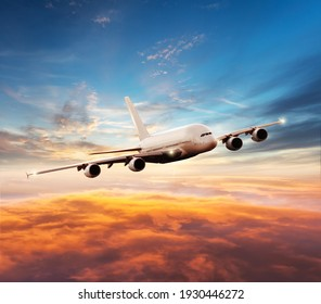 Passenger jetplane flying above clouds in sunset. Beautiful sunset scenery, transportation and fast travel concept.