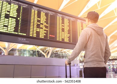 Passenger looking at departures board in airport terminal