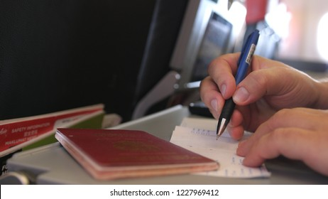 Passenger with passport is filling in the migration or arrival cards in the plane while flight