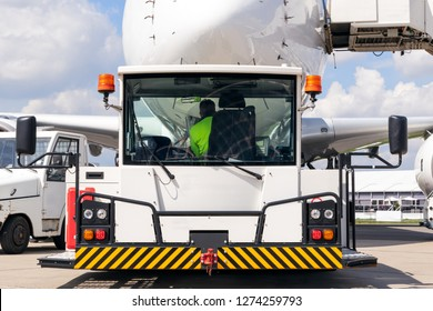 passenger plane about to be towed by an airport towing vehicle on the tarmac of an aerodrome.