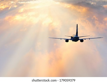 Passenger plane above the colorful clouds.