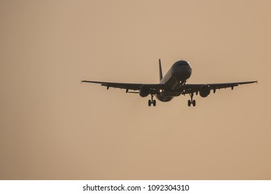 Passenger plane approaching to the airport during susnet