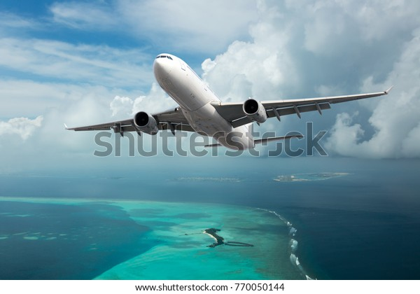 A passenger plane in the cloudy sky. Aircraft flies over the sea and the tropical island.
