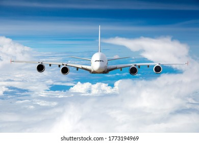 Passenger plane fies high over the clouds. Front view of the aircraft.