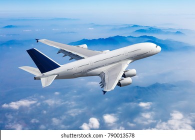 Passenger plane flies high over the clouds and mountain landscape. Aircraft top view.
