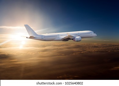 The passenger plane flies over the clouds during sunset. Side view of passenger long range aircraft.