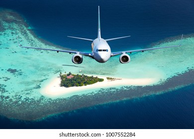 Passenger plane flies over the paradise Maldivian island and coral atoll