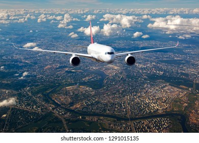 Passenger plane flies over the quarters of big city. Front view of aircraft.