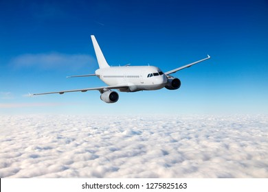A passenger plane flies in a transparent clear blue sky. The plane is flying over the clouds.