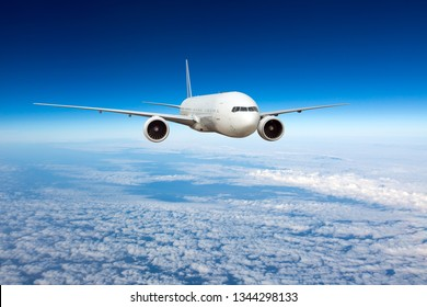 A passenger plane flies in a transparent clear blue sky. Aircraft flies over the clouds. Front view of aircraft.