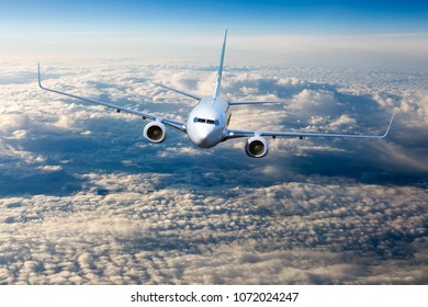 The passenger plane in flight. Aircraft flies high in the blue sky over clouds. Front view of airplane.
