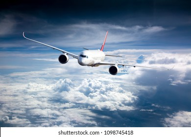 Passenger plane in flight. Aircraft flies high in the blue sky above the clouds. Front view. Right heeling.