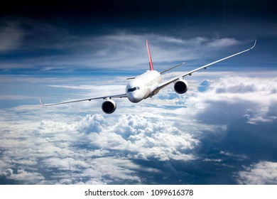 Passenger plane in flight. Aircraft flies high in the blue sky above the clouds. Front view. Left heeling.