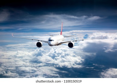 Passenger plane in flight. Aircraft flies high in the blue sky above the clouds. Front view.