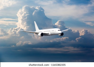Passenger plane in flight. The aircraft flies high in the sky above the storm clouds.