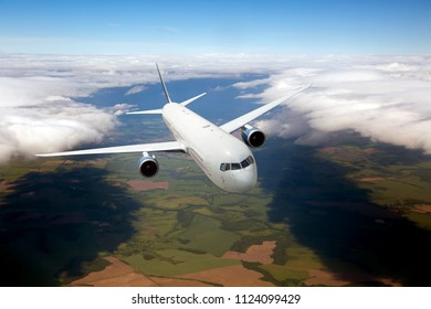 Passenger plane in flight. Aircraft fly high in the sky above green plain. Front view. Left heeling.
