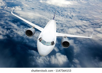 Passenger plane in flight. Aircraft fly high in the sky above the clouds. Front view. Right heeling.