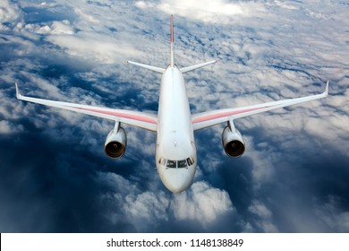 Passenger plane in flight. Aircraft fly high in the sky above the clouds. Front view.
