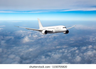 Passenger plane in flight. Aircraft fly high in the sky above the clouds. Front view of aircraft.