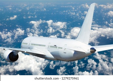 Passenger plane in flight. Aircraft fly high in the sky above the clouds. Back view of airplane.