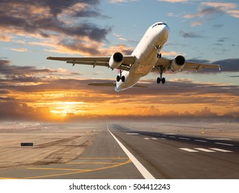 A passenger plane in flight. Aircraft takes off from the airport runway during sunset.