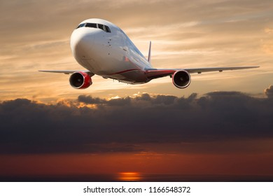 Passenger plane in flight. Front view of aircraft. Sunset time.