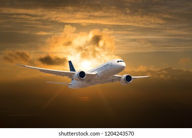 Passenger plane in flight. The plane on the background of the sunset orange sun. Front view of aircraft.
