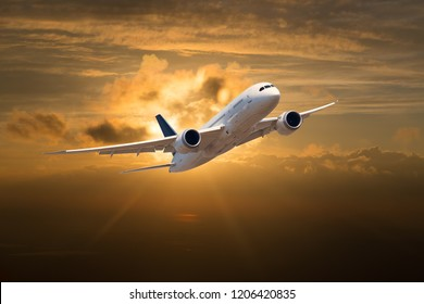 Passenger plane in flight. The plane on the background of the sunset orange sun. Front view of aircraft. Left heeling.