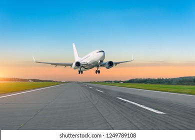 Passenger plane fly up over take off runway from airport at sunset