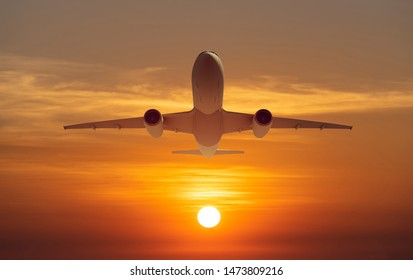passenger plane fly up over take-off runway from airport at sunset, sunrise