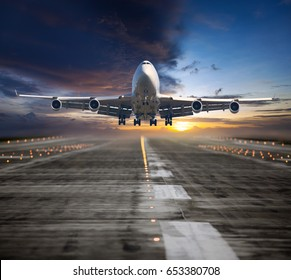 A passenger plane flying in the colorful sunset sky. Aircraft takes off from the airport runway. Airplane front view.
