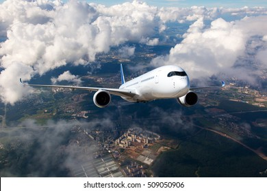 A passenger plane flying high in the clouds.  The aircraft flies over the city landscape.