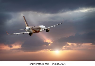 passenger plane flying in the stormy dramatic sky. the sun shines from behind the clouds. the plane flies