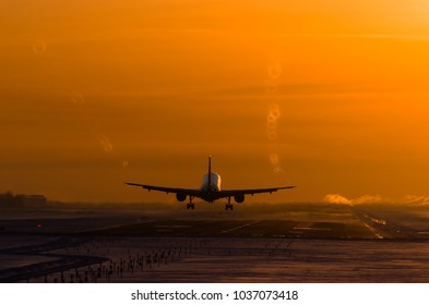 passenger plane is landing in the airport runway at early morning at sunrise time in the frosty winter air with vortexes